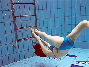 red-haired in blue swimsuit demonstrating her bod